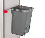 Plastic waste bin with metal frame that attaches it to an accessory bar on the side of a treatment trolley