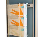 Estructura de metal con 3 cajas de cartón de guantes en su interior, con soporte que lo engancha a una barra porta accesorios