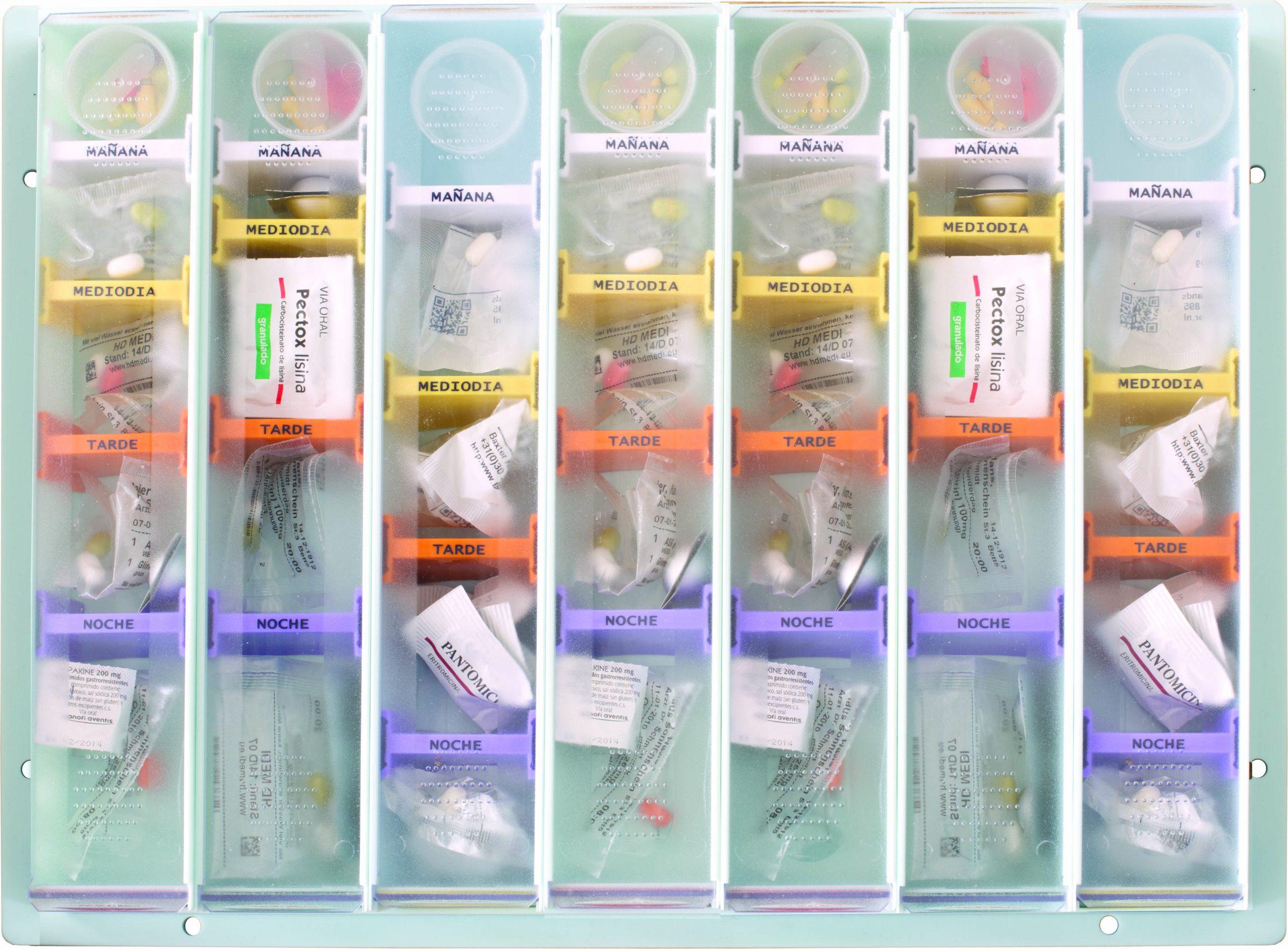 Bandeja semanal vista desde arriba con 7 pastilleros en su interior llenos de medicación, separada por divisores de colores